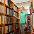 Young girl in the library looking for a book — Stock Photo #11540061