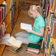Female university student reads a book in the library — Stock Photo #11540140