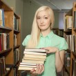 Female university student holding books in library — Stock Photo