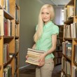 Female university student holding books in library — Stock Photo #11540239