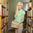 Stock Photo: Female university student holding books in library