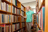 Young girl in the library looking for a book — Foto de Stock