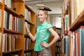 Female university student has fun in the library — Stock Photo