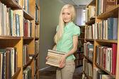женский университет студент холдинг книги в библиотеке — Стоковое фото