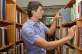 Young student in the library looking for a book — Stock Photo