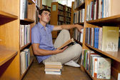 Male university student reads a book in the library — Stock Photo