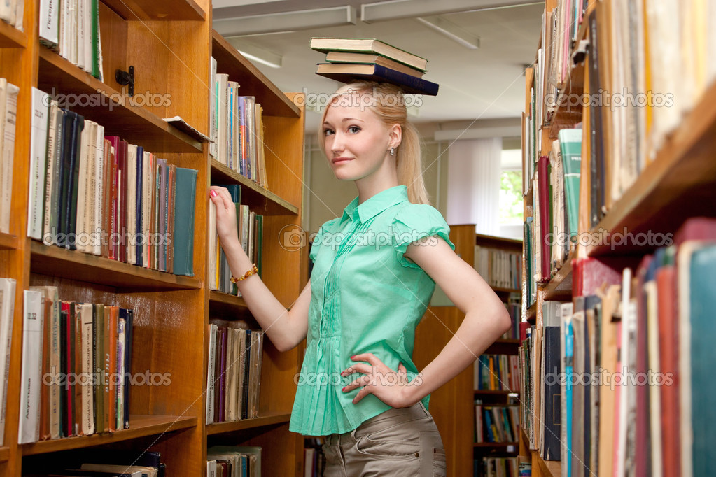 Young girl holds a book on her head — Stock Photo #11540107