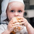 Portrait of a young boy who eats a bagel — Stockfoto