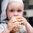 Portrait of a young boy who eats a bagel — Stock Photo