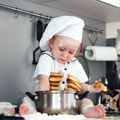 Portrait of a baby wearing a chef hat sitting inside a large cooking stock pot — Stock Photo