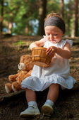 Little girl sitting on the ground with a basket and a bear — Stock Photo