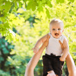 Little laughing baby in adult hands playing in park — Stock Photo