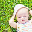 Stock Photo: Little dreaming baby laying on the grass