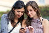 Two girlfriends in park with a mobile phone — Stock Photo