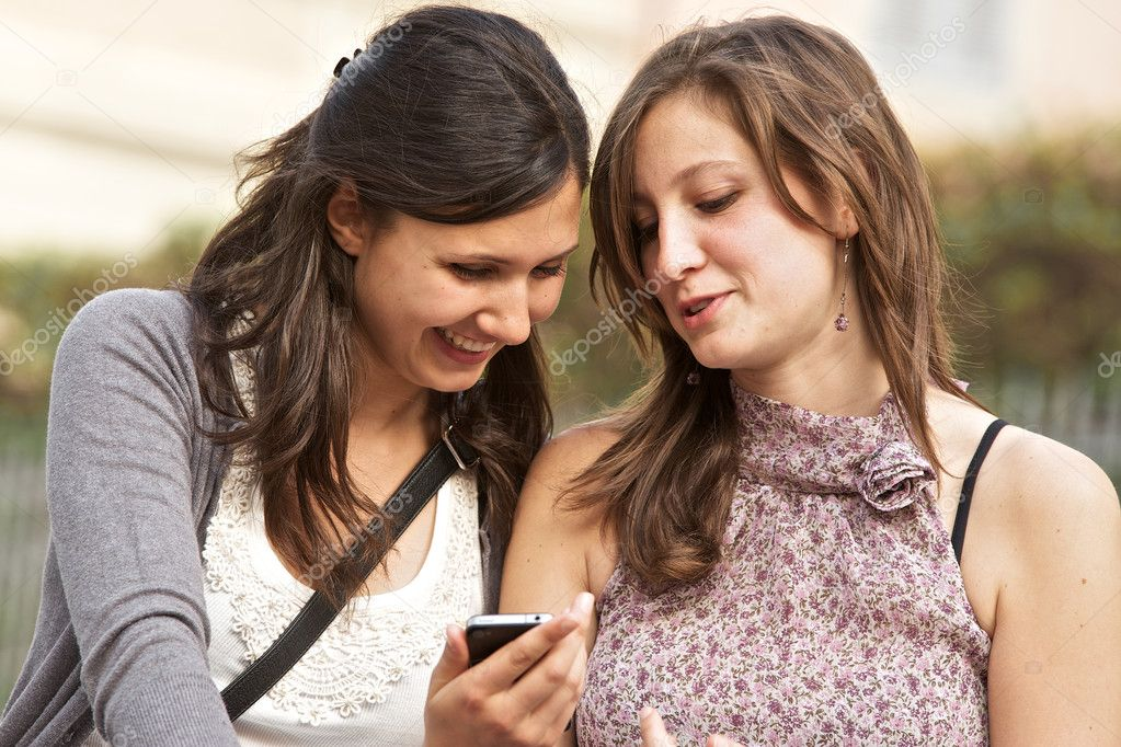 Two girlfriends in park with a mobile phone, italy — Stock Photo #10966987