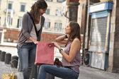 Jonge vrouwen in de stad na het winkelen — Stockfoto