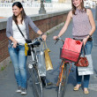Two Beautiful Women Walking in the City with Bicycles and Bags — Stock Photo #11058982