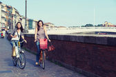 Two Beautiful Women Going by Bicycle — Stock Photo