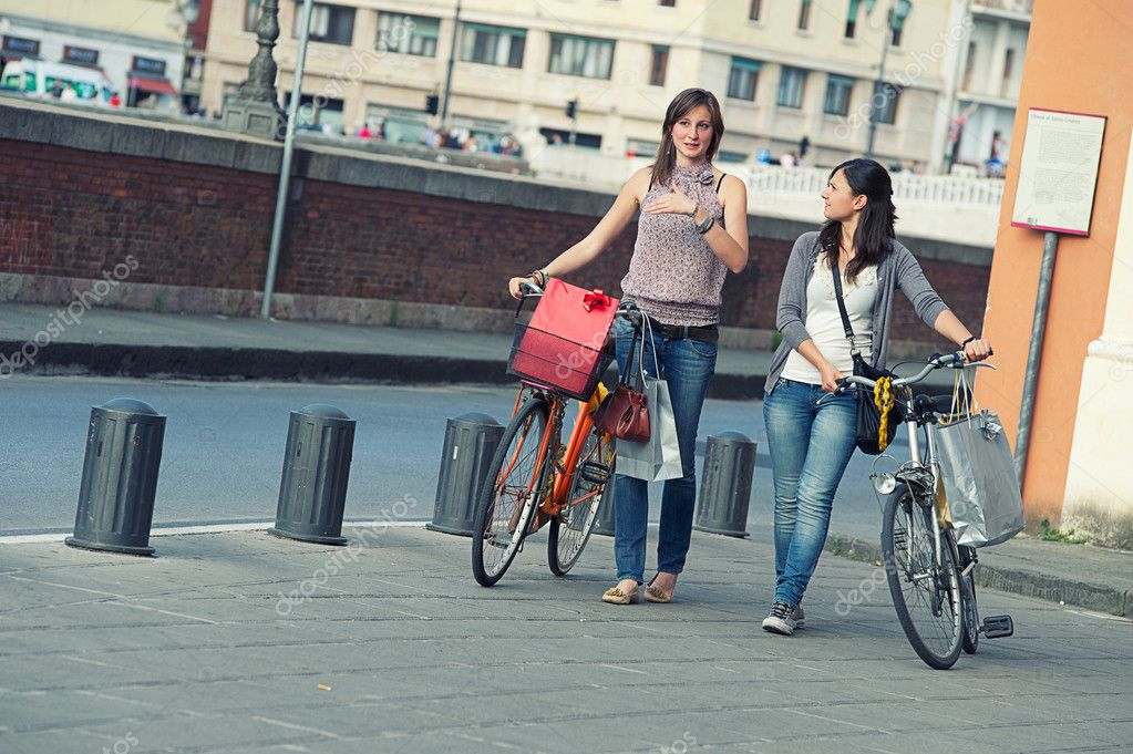 Two Beautiful Women Walking in the City with Bicycles and Bags — Stock Photo #11219559