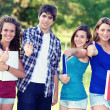 Young group of happy students showing thumbs up sign together - Foto Stock