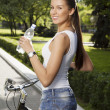 Girl with bicycle and bottle of water — Stock Photo