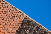 Red and old roof tiles and blue sky — Stock Photo