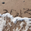 Numbers 2013 on beach sand with wave water — Stock Photo