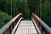 Small wooden footbridge over stream — Stock Photo