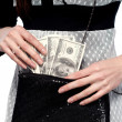A young girl pulls dollars out of the bag. On a white background — Stock Photo