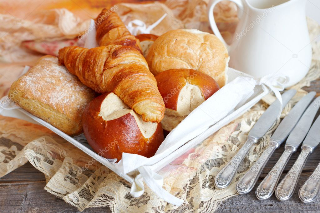 Various types of bread like French croissants, Italian ciabatta, German buns and other with silver knives — Stock Photo #12046445