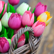 Colorful wooden tulips in a basket - Stock Photo