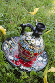 Antique jug with flowers — Stock Photo