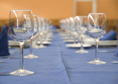 A table with a row of glasses and cutlery — Stock Photo