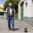 Elderly man walking a dog — Stock Photo