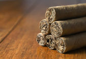 Cigars habanos huddled on wood background — Stock Photo