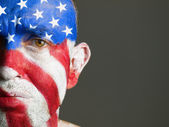 Man face painted with the flag of USA, sad expression — Stock Photo