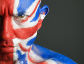 Man with his face painted with the flag of United Kingdom — Stock Photo