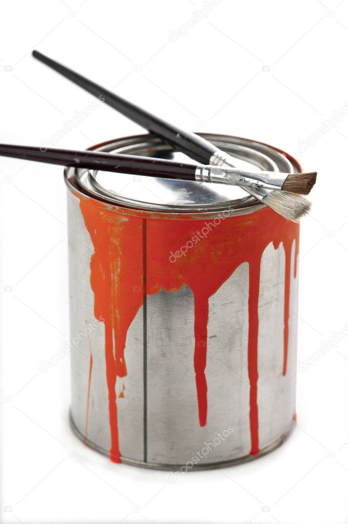 Two artists fine art paintbrushes resting on top of a paint can with orange paint dripping down the side of the can   #11234145