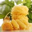 Various types of pasta with basil and tomatoes — Stock Photo