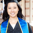Beautiful young asian woman in graduation cap and gown - Stock Photo