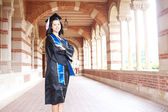 Beautiful young asian woman in graduation cap and gown — Stockfoto