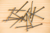 Heap of iron nails on wooden floor — Stock Photo