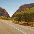Desert road and wild nature at Simpsons Gap, Australia - Stock Photo