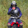 Постер, плакат: Samurai in armor drinking from bowl