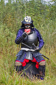 Samurai in armor drinking from bowl — Stock Photo