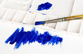 Old paint brush and palette with blue painting — Stockfoto