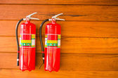 Extinguisher on wooden wall — Stock Photo