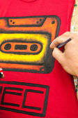Street artist paints a t-shirt — Stock Photo