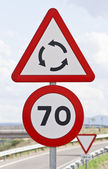 Traffic signs that warn of speed limitation, and roundabout — Zdjęcie stockowe
