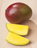 Whole and sectioned Mango on wood base — Stock Photo